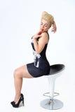 Blonde Frau, die auf einem Stuhl im Studio sitzt Lizenzfreie Stockfotografie
