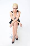 Blonde Frau, die auf einem Stuhl im Studio sitzt Stockfotos