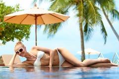 Blonde Frau, die auf einem Unendlichkeitspool ein Sonnenbad nimmt Lizenzfreie Stockfotografie