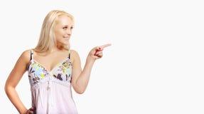 Blonde Frau, die auf einen leeren Anzeigen-Platz zeigt Lizenzfreies Stockbild