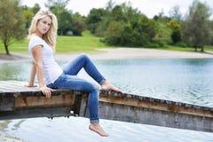 Blonde Frau, die auf einer Anlegestelle sitzt Stockfotografie