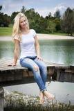 Blonde Frau, die auf einer Anlegestelle sitzt Lizenzfreies Stockfoto