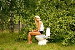 Blonde Frau, die auf einer Toilettenschüssel sitzt und ein Buch liest Stockfotos