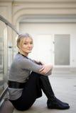 Blonde Frau, die auf Fußboden am großen Speicher sitzt Stockfoto