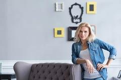 Blonde Frau, die auf grauer Couch sich lehnt Lizenzfreies Stockfoto