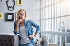 Blonde Frau, die auf grauer Couch sich lehnt Stockbilder