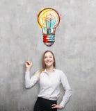 Blonde Frau, die auf große bunte Glühlampe zeigt Lizenzfreies Stockbild