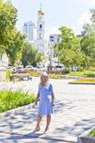 Blonde Frau, die auf Kirchenhintergrund steht Lizenzfreies Stockbild