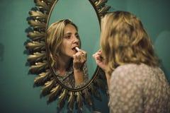 Blonde Frau, die auf Lippenstift sich setzt Stockfotografie