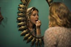 Blonde Frau, die auf Lippenstift sich setzt Lizenzfreies Stockbild