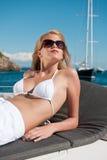 Blonde Frau, die auf Luxuxyacht mit Bikini ein Sonnenbad nimmt Lizenzfreies Stockbild