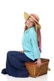 Blonde Frau, die auf Picknickkorb sitzt Lizenzfreie Stockfotografie
