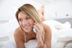 Blonde Frau, die auf Smartphone spricht Lizenzfreie Stockbilder