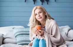 Blonde Frau, die auf Sofa mit Schale sitzt Stockbild