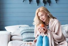 Blonde Frau, die auf Sofa mit Schale sitzt Lizenzfreie Stockfotos