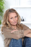 Blonde Frau, die auf Sofa sich entspannt Lizenzfreie Stockfotos