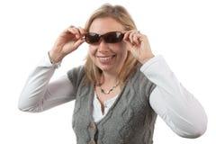 Blonde Frau, die auf Sonnenbrillen sich setzt Lizenzfreies Stockbild