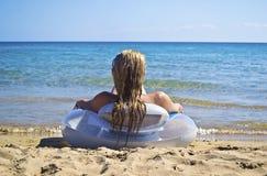 Blonde Frau, die auf Strand Griechenland sitzt Lizenzfreie Stockfotografie