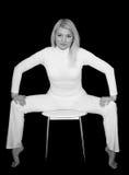 Blonde Frau, die auf Stuhl sitzt Stockfotos
