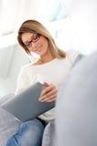 Blonde Frau, die auf Tablette websurfing ist Lizenzfreies Stockfoto