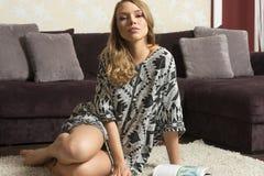 Blonde Frau, die auf Teppich aufwirft Lizenzfreie Stockbilder
