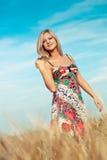 Blonde Frau, die auf Weizenfeld geht Stockfoto