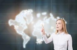 Blonde Frau, die auf Weltkarte einwirkt Stockfoto
