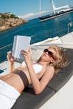 Blonde Frau, die auf Yachtlesebuch liegt Stockbild