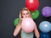 Blonde Frau, die Ballone für eine Partei aufbläst Lizenzfreie Stockfotografie