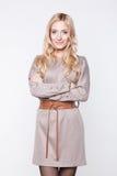 Blonde Frau, die beige Kleid mit Gurt trägt Stockbilder
