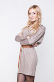 Blonde Frau, die beige Kleid mit Gurt trägt Lizenzfreies Stockfoto