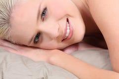 Blonde Frau, die in Bett legt Lizenzfreie Stockfotografie