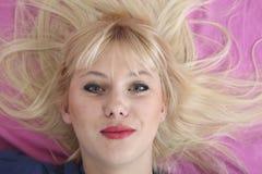 Blonde Frau, die am Bett legt und an der Kamera zuschließt Stockfotos
