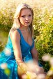 Blonde Frau, die blaues Kleid auf einem Feld trägt Stockfotos