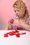 Blonde Frau, die Blumenblätter einer Rose nimmt Stockfotografie