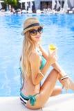 Blonde Frau, die Cocktail nahe dem Swimmingpool genießt Stockfotografie