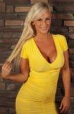 Blonde Frau, die das gelbe Kleidlächeln trägt Stockbild