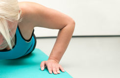 Blonde Frau, die das Handeln drückt, ups an der Gymnastik Stockfoto