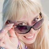 Blonde Frau, die das Kameralächeln betrachtet Lizenzfreie Stockfotografie