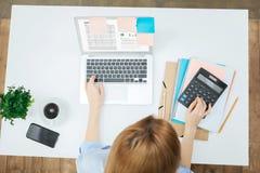 Blonde Frau, die an dem Laptop an ihrem Tisch arbeitet Stockfoto