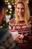 Blonde Frau, die dem Mann Weihnachtsgeschenk gibt Lizenzfreies Stockfoto