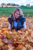 Blonde Frau, die in den gelben Blättern aufwirft Stockfotografie