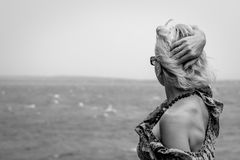 Blonde Frau, die den Horizont betrachtet Stockfoto
