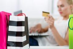 Blonde Frau, die den Kauf über das Internet zahlt Kreditkarte abschließt Stockfotografie