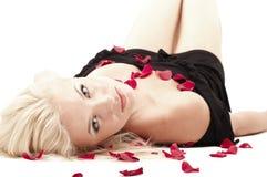 Blonde Frau, die in den rosafarbenen Blumenblättern liegt Lizenzfreie Stockfotografie