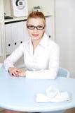 Blonde Frau, die den Schreibtisch behing sitzt. Stockbilder
