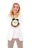 Blonde Frau, die den Wecker, lokalisiert auf Weiß zeigt Lizenzfreie Stockfotos