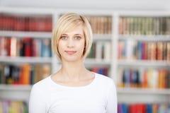 Blonde Frau, die in der Bibliothek steht Stockbilder