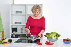Blonde Frau, die in der Küche kocht Lizenzfreie Stockfotografie