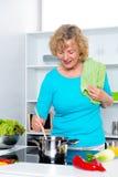 Blonde Frau, die in der Küche kocht und backt Stockfotos